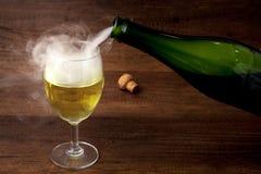 Vin ou champagne de versement de la bouteille verte dans le verre de vin avec de la fumée sur le fond en bois, pour la célébratio Photographie stock libre de droits
