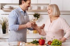 Vin potable d'homme agréable avec sa mère dans la cuisine Image stock