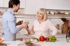 Vin potable d'homme barbu avec sa mère dans la cuisine Images libres de droits