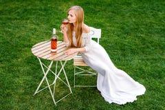 Vin potable de belle femme en café d'extérieur Portrait de jeune beauté blonde dans les vignobles ayant l'amusement, appréciant a Photo stock