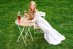 Vin potable de belle femme en café d'extérieur Portrait de jeune beauté blonde dans les vignobles ayant l'amusement, appréciant a Photos stock