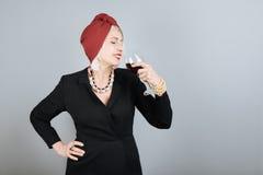 Vin potable de belle femme supérieure avec du charme Images stock