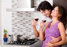 Vin potable de couples dans leur cuisine Photographie stock libre de droits