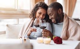 Vin potable de couples joyeux d'Afro-américain dans le restaurant Photographie stock libre de droits
