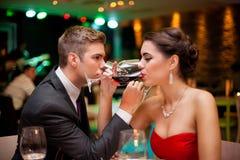 Vin potable de couples romantiques Photographie stock libre de droits