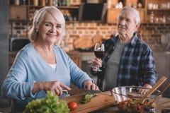 Vin potable de couples supérieurs et cuisson ensemble Photographie stock