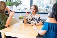 Vin potable de femme attirante avec des amis au café Photographie stock libre de droits