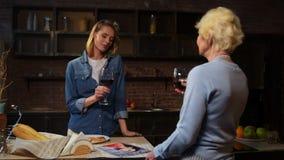 Vin potable de femme attirante gaie avec sa mère pluse âgé dans la cuisine clips vidéos