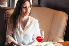 Vin potable de femme blonde attirante dans l'intérieur de luxe Images stock