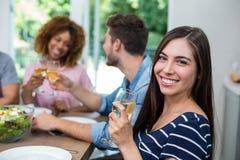 Vin potable de jeune femme heureuse avec des amis Photographie stock libre de droits