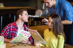 Vin potable de jeune homme et de femme dans un restaurant Vin potable de jeune homme et de femme une date Homme et femme une date Photographie stock libre de droits