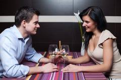 Vin potable de jeunes couples et flirt Photographie stock libre de droits