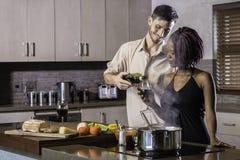 Vin potable de jeunes couples heureux de métis faisant cuire le dîner dans la cuisine Image libre de droits