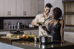 Vin potable de jeunes couples heureux de métis faisant cuire le dîner dans la cuisine Photos stock