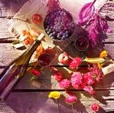 Vin, raisins et fleurs sur la table en bois sale Photos libres de droits