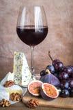 Vin rouge avec du fromage, des figues et des raisins Photographie stock