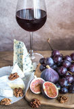 Vin rouge avec le camembert, les figues et les raisins Image stock