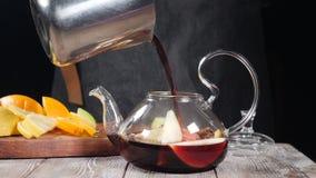 Vin rouge chaud de versement dans la théière avec le fruit coupé en tranches La théière en verre avec l'orange et le citron à l'i clips vidéos