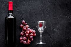 Vin rouge de goût Bouteille du vin rouge, du verre et du raisin rouge sur le copyspace noir de vue supérieure de fond photographie stock