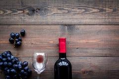 Vin rouge de goût Bouteille de raisin de vin, en verre et noir rouge sur le copyspace en bois foncé de vue supérieure de fond image libre de droits