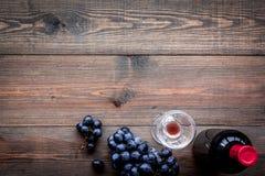Vin rouge de goût Bouteille de raisin de vin, en verre et noir rouge sur le copyspace en bois foncé de vue supérieure de fond photographie stock