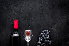Vin rouge de goût Bouteille de raisin de vin, en verre et noir rouge sur le copyspace en pierre noir de vue supérieure de fond photographie stock libre de droits