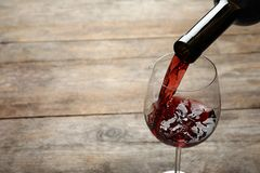 Vin rouge de versement de bouteille dans le verre sur le fond en bois photo libre de droits
