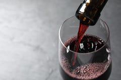 Vin rouge de versement de bouteille dans le verre sur le fond gris L'espace pour le texte images stock