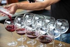 Vin rouge de versement de décanteur dans le verre à vin sur la rangée des verres Fermez-vous du vin rouge pour entretenir l'établ Image stock