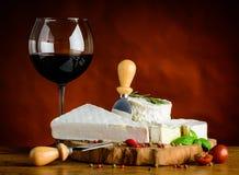 Vin rouge en verre et fromage à pâte molle Images stock