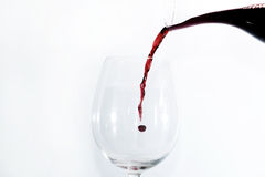 Vin rouge pleuvant à torrents dans une glace Image libre de droits