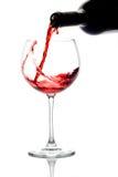 Vin rouge pleuvant à torrents vers le bas d'une bouteille de vin Images libres de droits