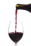 Vin rouge pleuvant à torrents vers le bas d'une bouteille de vin d'isolement Photos stock