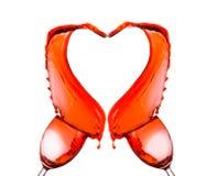 Vin rouge renversant et formant la forme de coeur Photo libre de droits