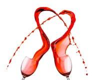 Vin rouge renversant et formant la forme de coeur Image stock