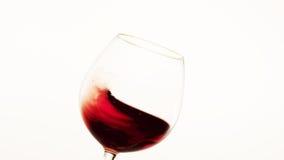 Vin rouge se déplaçant au côté gauche d'un verre images stock