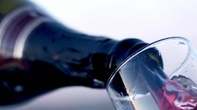 Vin rouge versant dans la vue en verre d'angle faible dans le mouvement lent r