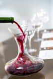 Vin rouge versant dans le décanteur à l'échantillon de vin Images stock