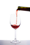 Vin rouge versant dans le verre de vin Photo stock