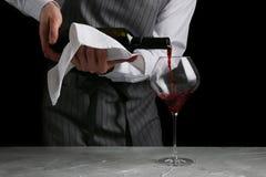 Vin rouge versant en verre barman sur le concept de serveur sur le fond noir image libre de droits