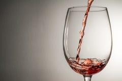 Vin som plaskar, färgstänk, ström av vin som hälls in i ett isolerat exponeringsglas Fotografering för Bildbyråer