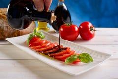 Vinagre balsámico sobre los tomates imágenes de archivo libres de regalías