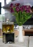 Vinagre balsámico y aceite de oliva, florero próximo con las flores Fotos de archivo