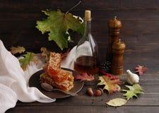 Vinagre balsâmico, moinho de pimenta da madeira e mel nos favos de mel em uma placa Foto de Stock