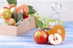 Vinagre de Apple con las manzanas maduras en un fondo de madera azul foto de archivo