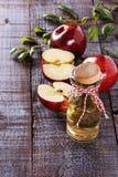 Vinaigre et pommes de cidre d'Apple au-dessus du fond en bois blanc Photo stock