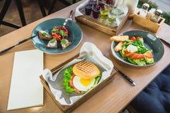Vinaigrette salad, american burger with egg, Caesar salad and drinks. On table stock images