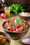 Festive beetroot salad vinaigrette in a clay bowl. Vinaigrette salad with boiled vegetables, pickled cucumbers, sauerkraut and canned green peas in a clay bowl Royalty Free Stock Images
