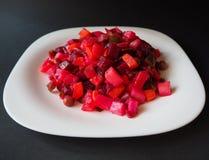 Vinaigrette vegetarian salad on the white plate. Side view stock image