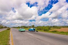 VINALES,古巴- 2017年5月13日:在路的美国减速火箭的汽车 复制文本的空间 库存图片